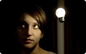 Kreativitätstechniken symbolisiert durch schwebende Glühbirne neben Person