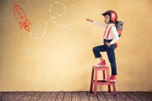 Kind vor Wand mit Rakete will Innovationen umsetzen