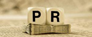 Würfel mit Aufdruck PR auf Zeitungsstapel