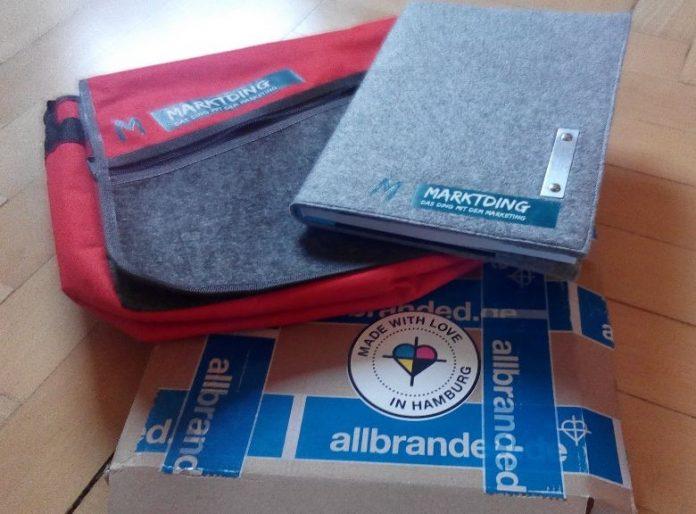 mi dem Marktding-Logo personalisierte Tasche und Notizblok von allbranded.de mit Verpackung