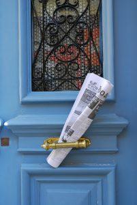 Zeitung an Haustür mit Haushaltswerbung